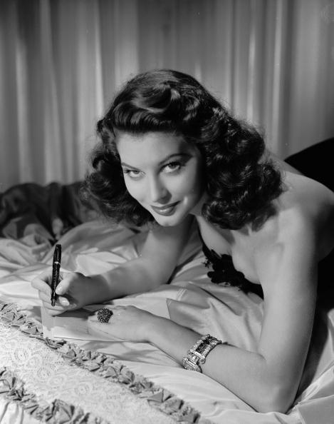 2nd June 1944:  Actress Ava Gardner (1922 - 1990) reclining on a bed to write a letter.  (Photo by Clarence Sinclair Bull/John Kobal Foundation/Getty Images)